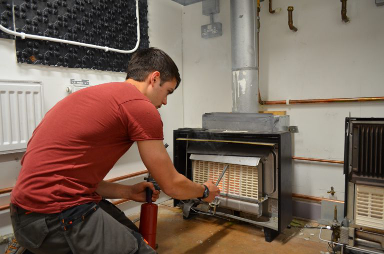 Student looking at heater as part of his HTR1 Heaters 和 Fires Re-assessment course.