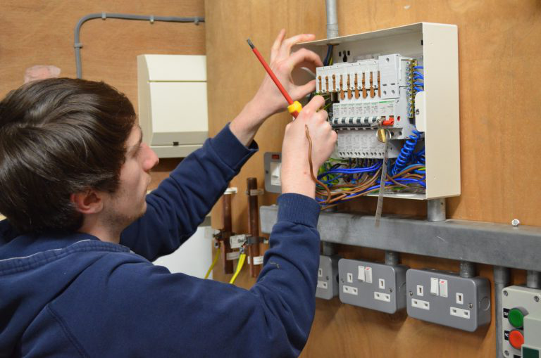 电动 student working at a fuse board.