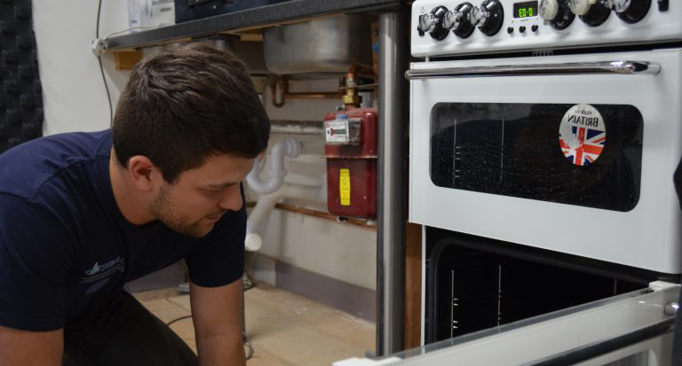 Student looking at gas cooker as part of his CKR1 Gas Cookers Re-assessment course.