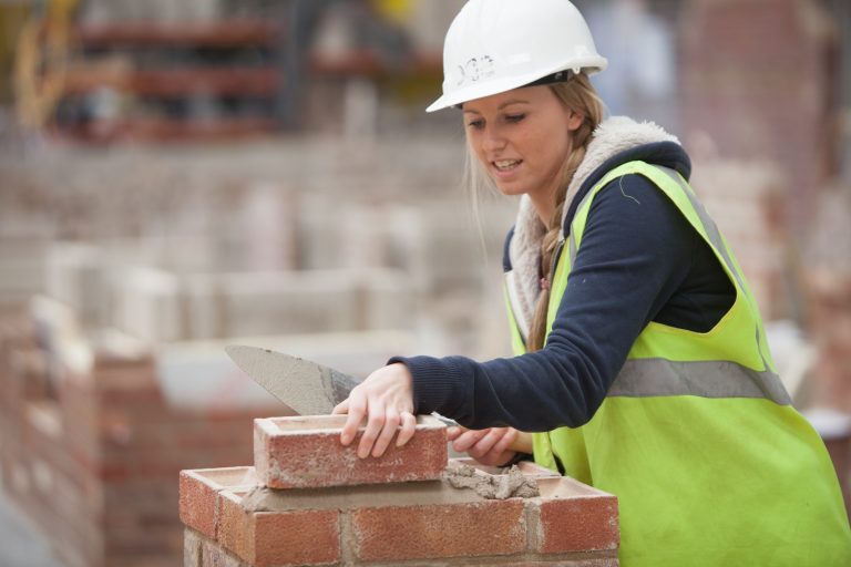 Female bricklaying student.