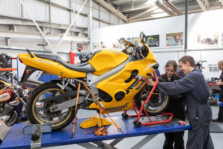 Motorcycle students working on yellow bike.