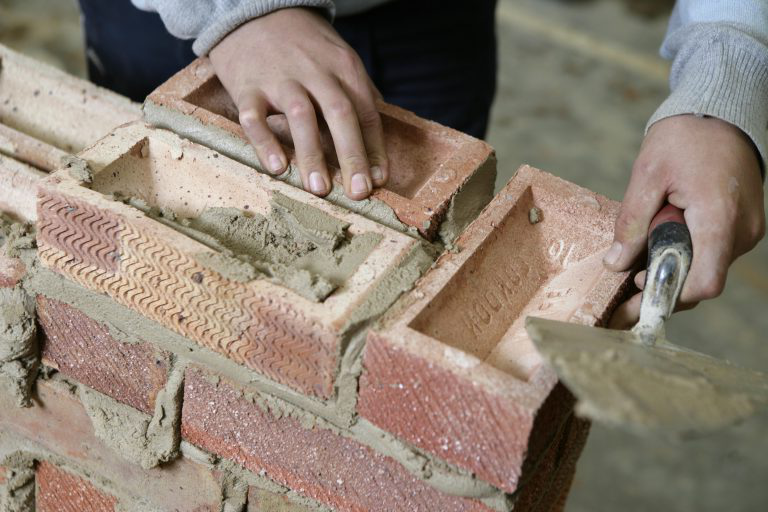 Close up shot of student laying a brick.