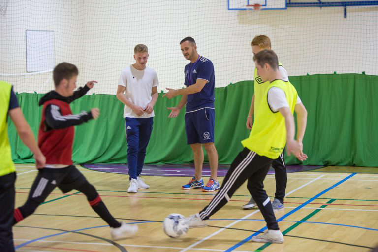 Students playing football in sports hall.