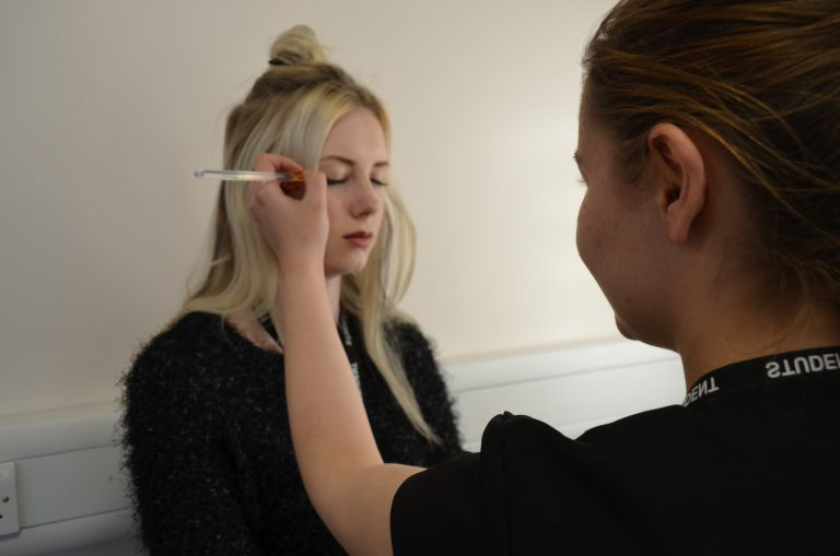 Beauty student putting on make up.