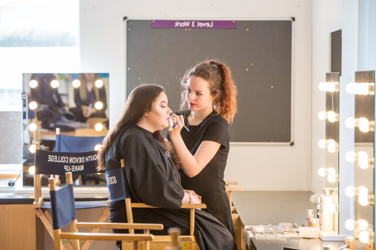 Student applying make up to client.