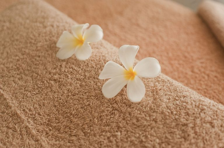 Towel with two flowers placed on top in spa.